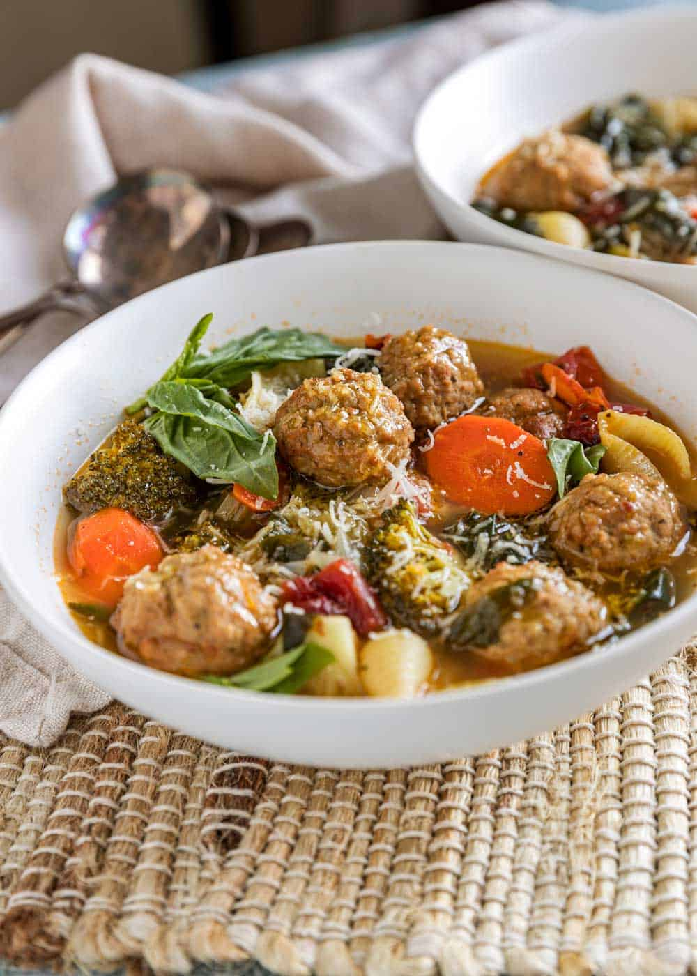 bowl of meatball soup in white bowl on place mat