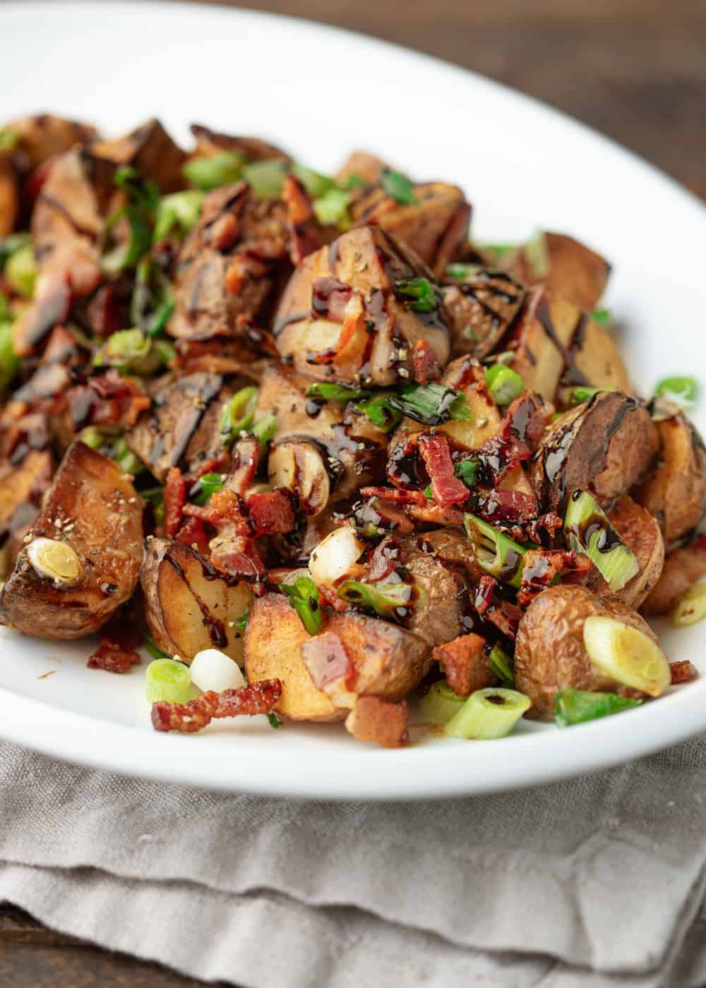 potatoes on white platter with bacon and green onions