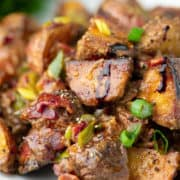 close up of a fried potato with bacon and green onions