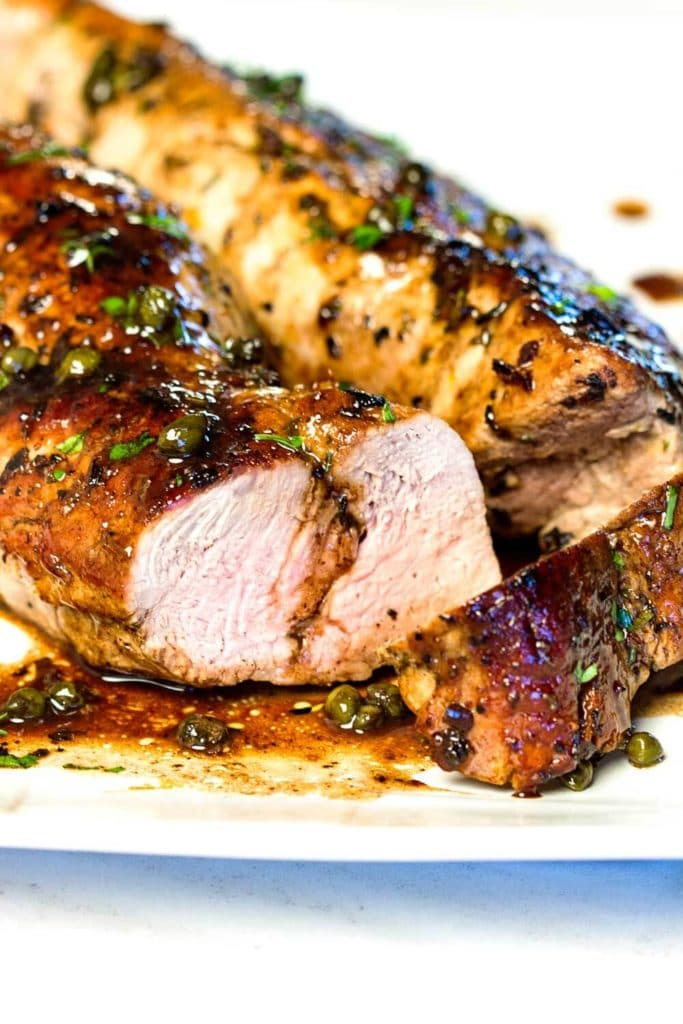 close up of roast pork tenderloin with capers and balsamic glaze