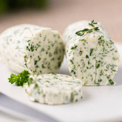 cylindrical roll of herb butter (compound butter)