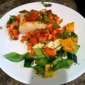 A plate of sea bass with Salsa and Strawberry