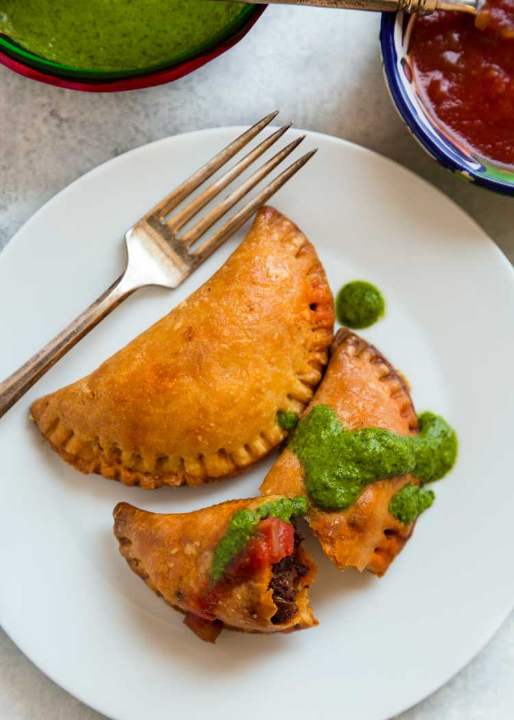 Empanadas Mendocinas are traditional Argentinean baked empanadas filled with beef, onions, warm spices, hard-boiled egg and olives. Dough recipe included! keviniscooking.com