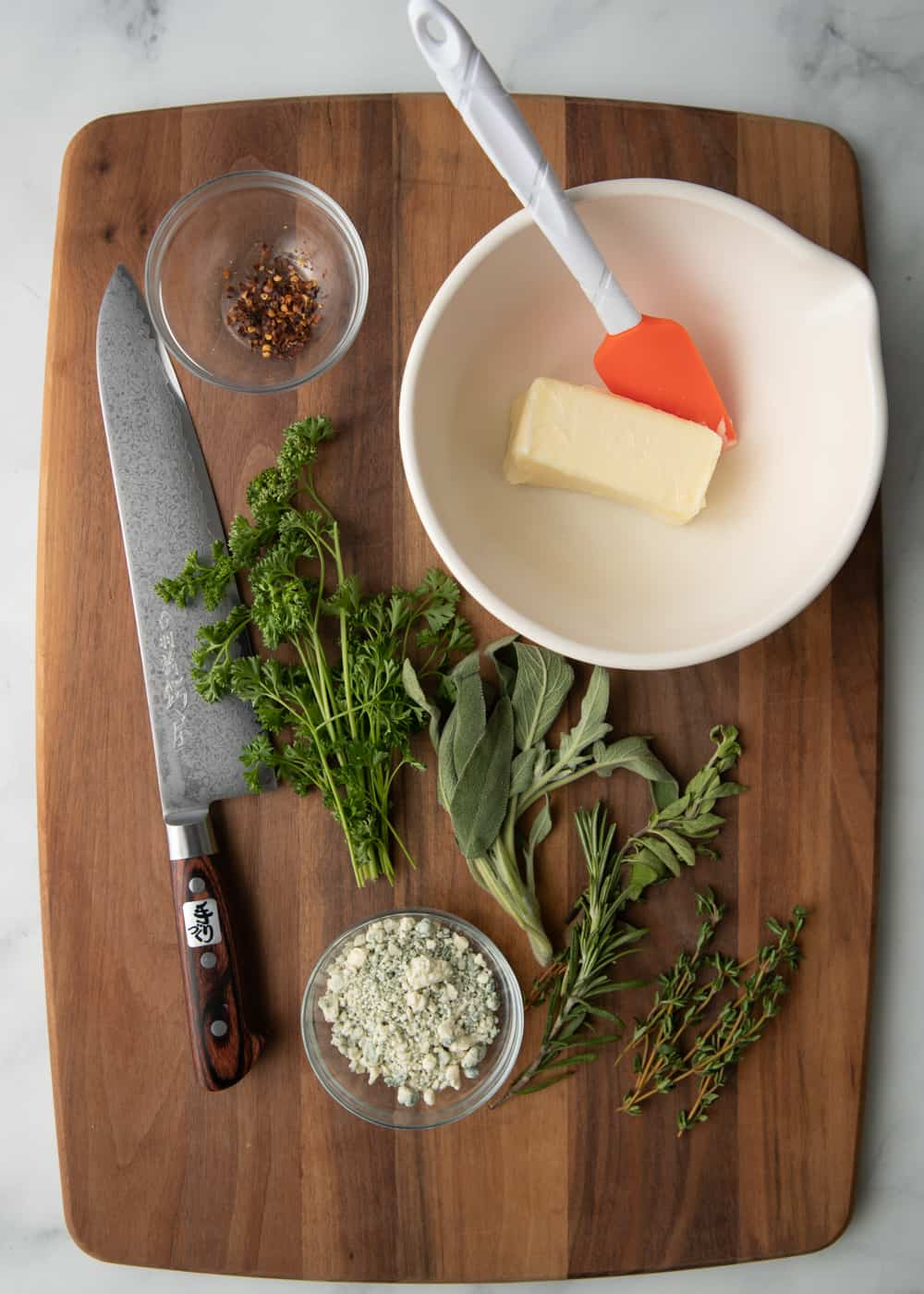 chefs knife, fresh herb and spices with soft butter on wooden cutting board to make compound butter for steak