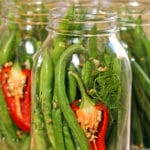 A close up of a green beans, chile in glass jar