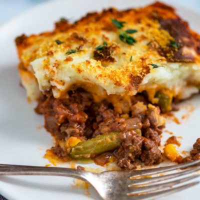 Easy Cottage Pie has ground beef simmered with onions, garlic, thyme in a savory red wine and tomato that's topped with vegetables and then mashed potatoes.