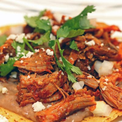 A plate of food, with Pork and Tostada