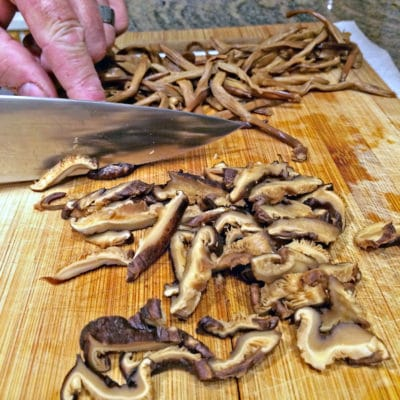 A wooden cutting board, with sliced mushrooms