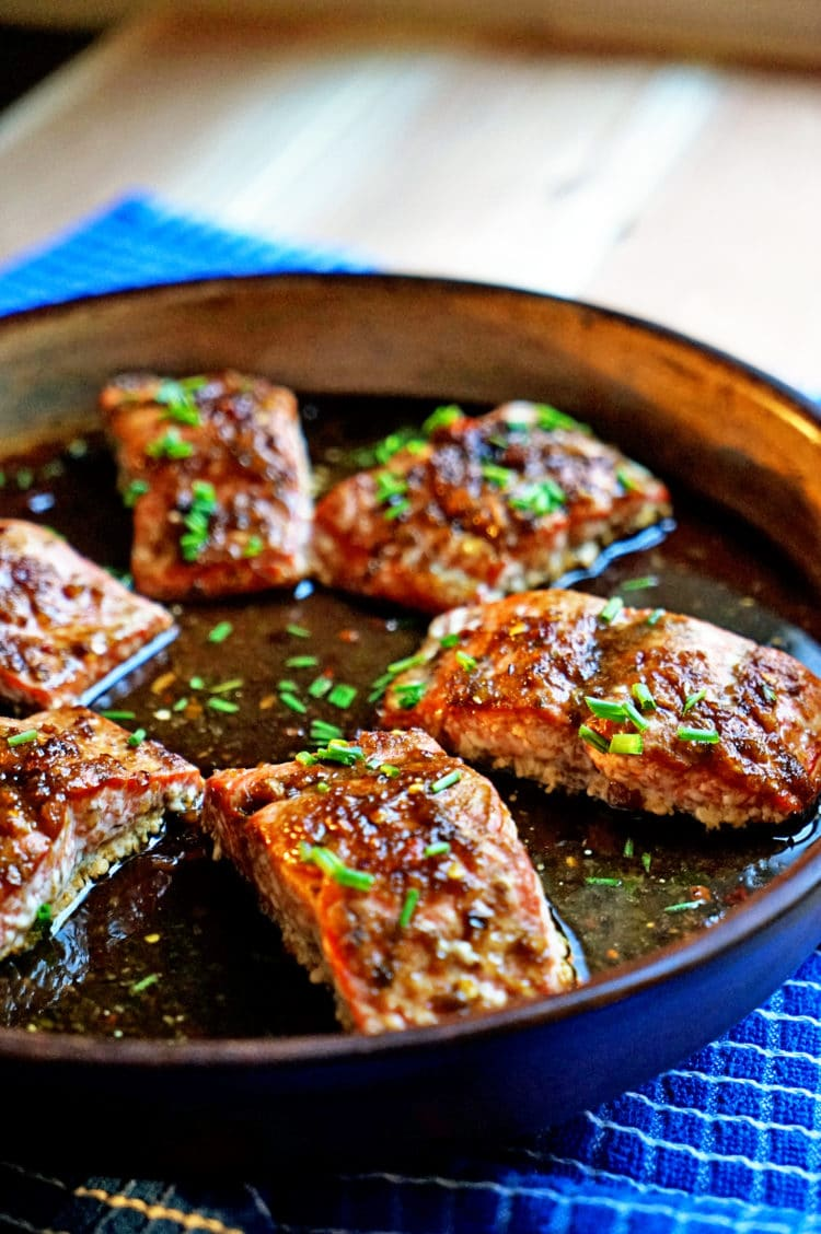 salmon glazed filet sin baking dish with chopped chives