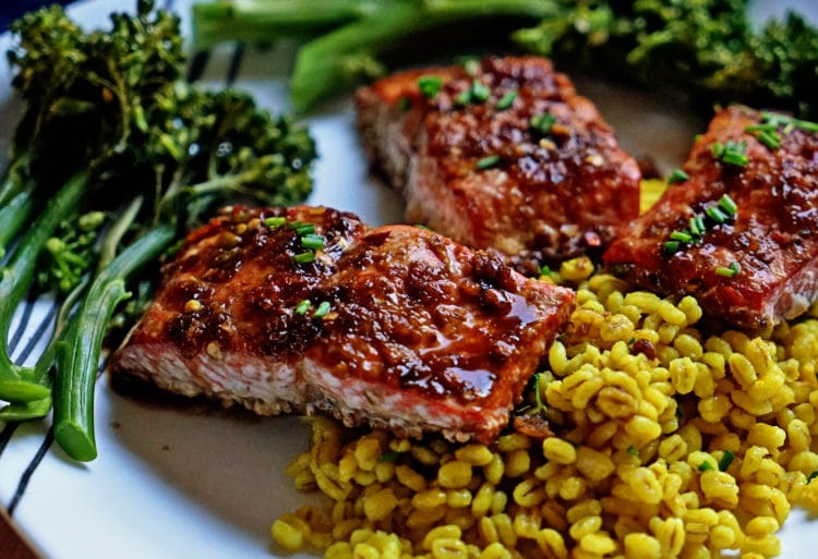 salmon glazed filet sin baking dish with chopped chives with barley