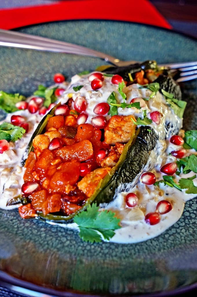 Chiles en Nogada, roasted poblano chiles stuffed with chicken, fruit and vegetables topped with a white wine, onion, cream reduction with ground walnuts. keviniscooking.com