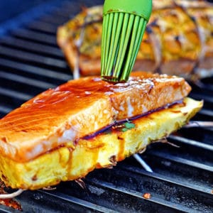 Teriyaki Glazed Grilled Salmon Pineapple Planks. Salmon filet lay on cilantro, is basted with teriyaki sauce before grilling between 2 pineapple planks. keviniscooking.com