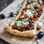 This Greek Feta Lamb Tart is made with warm spices, ground lamb, olives, feta cheese and puff pastry. Delivers big on flavor! keviniscooking.com