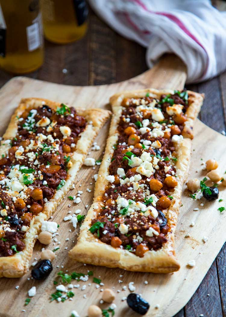This Greek Lamb Feta Tart is made with warm spices, ground lamb, olives, feta cheese and puff pastry. Delivers big on flavor! keviniscooking.com