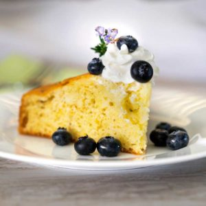 A close up of a piece of lemon rosemary cake on a plate with blueberries