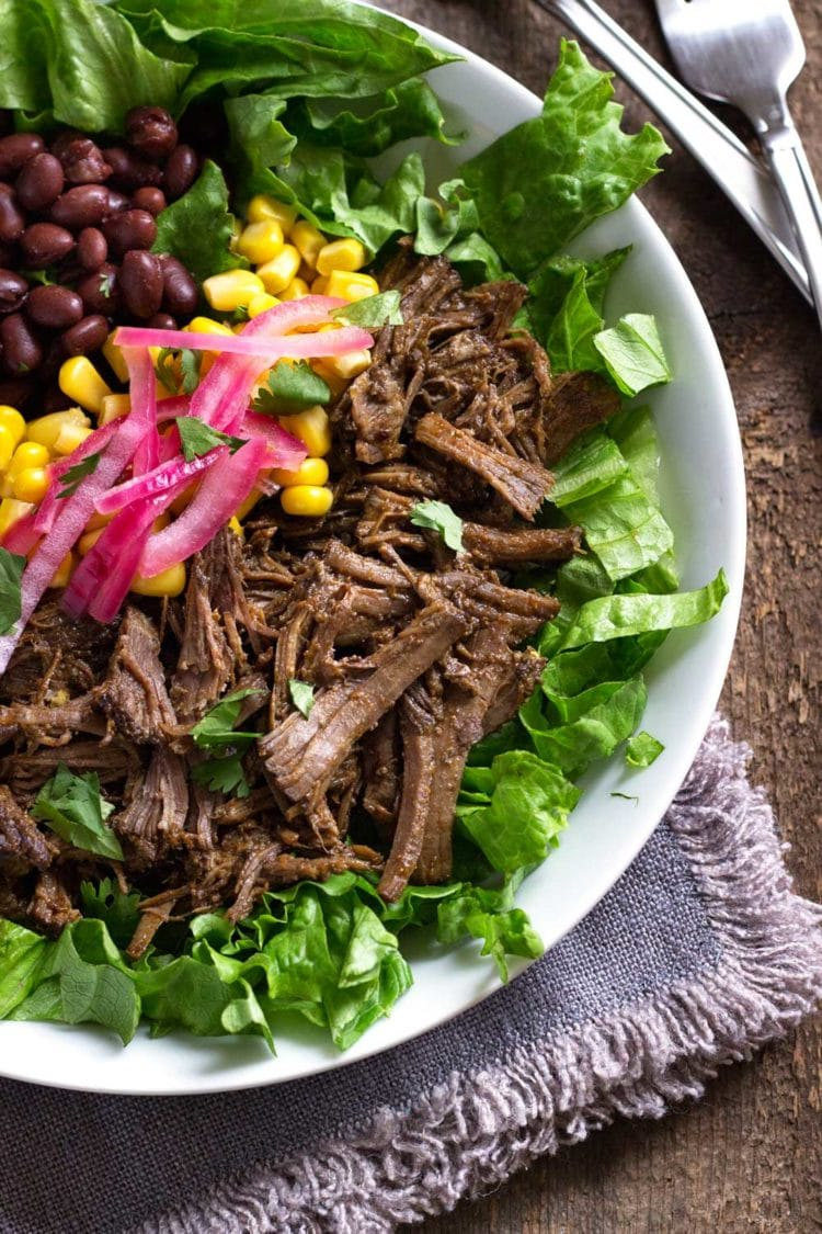 This slow cooker beef is simmered in chipotle, adobo, vinegar, citrus juice and spices for fall apart delicious shredded beef. Perfect in a salad or tacos. www.keviniscooking.com