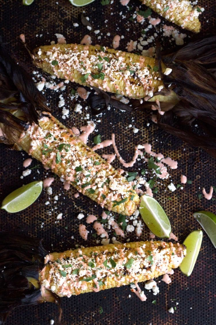 Grilled Corn with Cotija and Sriracha Crema and limes