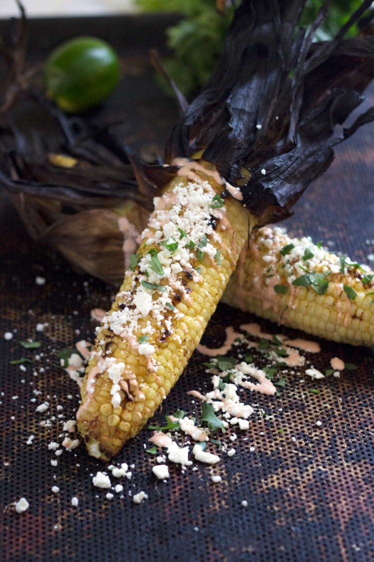 close up of an ear of Elote. Grilled Corn with Cotija and Sriracha Crema.