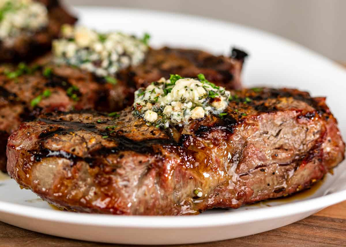 grilled ribeye steaks topped with blue cheese steak butter on white platter