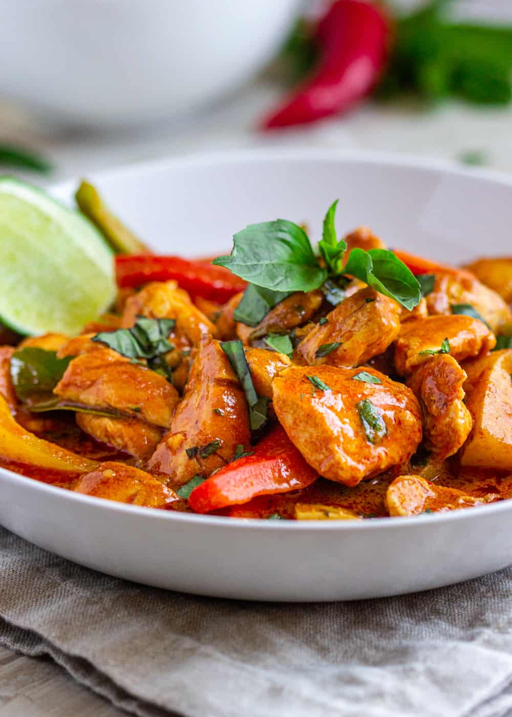 Thai Red Curry with Chicken in white bowl with lime slice