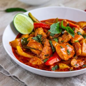 red curry sauced chicken pieces in white bowl