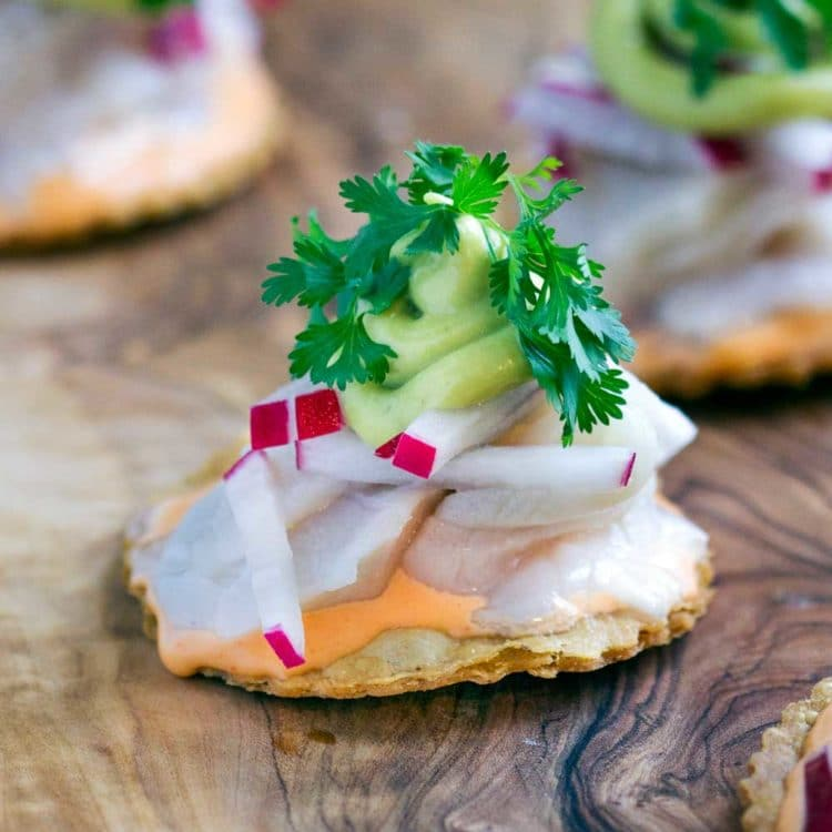 These crispy, hand held Baja Yellowtail Tostadas are made with fresh fish tossed in lime juice, a spicy sauce, radishes, avocado mousse and cilantro. www.keviniscooking.com