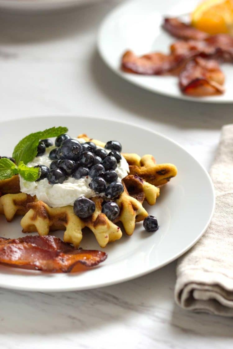 Fresh, warm Blueberry Poundcake Waffles served up. These tender and buttery waffles are laced with fresh berries, a great way to start your day! www.keviniscooking.com