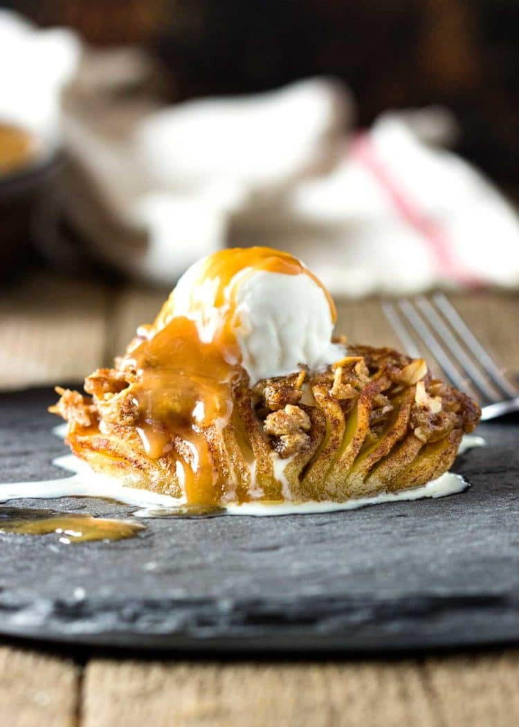 These Baked Hasselback Apples open like a fan and the sweet streusel melts in between each slice for one tasty dessert. Topped with ice cream and caramel. A must the whole family LOVES! www.keviniscooking.com