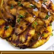 grilled chicken and pinapple with sauce on white platter