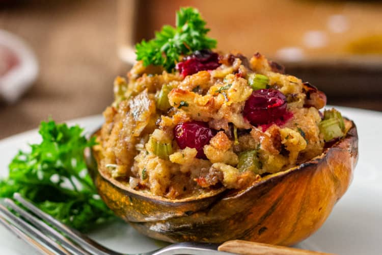 sausage stuffing inside of baked acorn squash on plate with fork