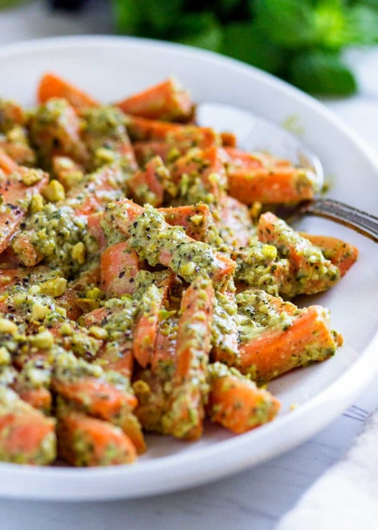 These Carrots with Pistachio Herb Butter get crunch appeal from pistachios sprinkled on top and in a wonderful lime and mint butter. It's the unexpected pop of freshness in the herb butter coat them that makes this special. A tasty side dish that is a new house favorite. www.keviniscooking.com
