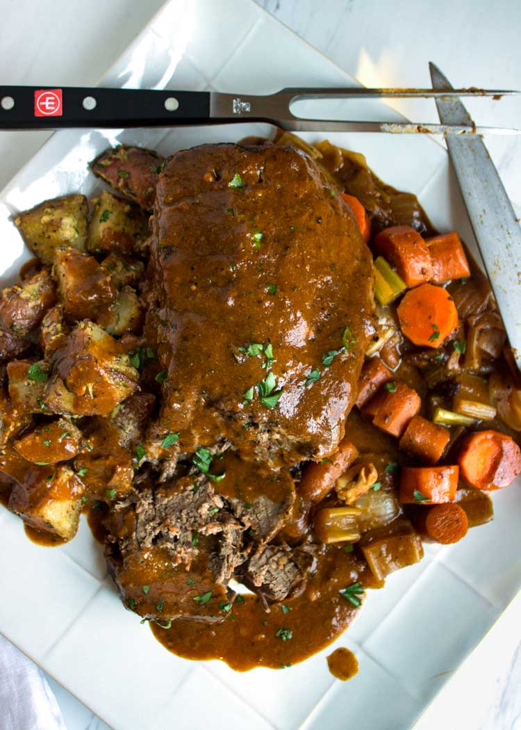 Melt in your mouth Slow Cooker Pot Roast, so fall apart tender and the gravy is made from blending half of the cooked vegetables with the cooking marinade. www.keviniscooking.com