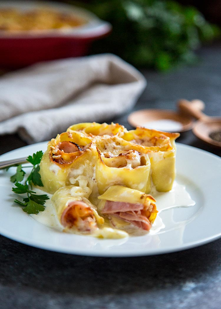 Ham and Cheese Pasta Rosettes start with fresh pasta sheets, sliced ham, fontina or provolone cheese. Roll up, cover with with cream and nutmeg and bake! keviniscooking.com