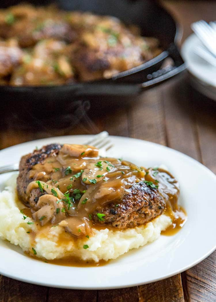 This Salisbury Steak with Mushroom Gravy is a great from scratch recipe straight from one of mom's archive recipe cards. A savory salisbury steak dinner with an onion, mushroom gravy that is perfect served over mashed potatoes for comfort food goodness. keviniscooking.com