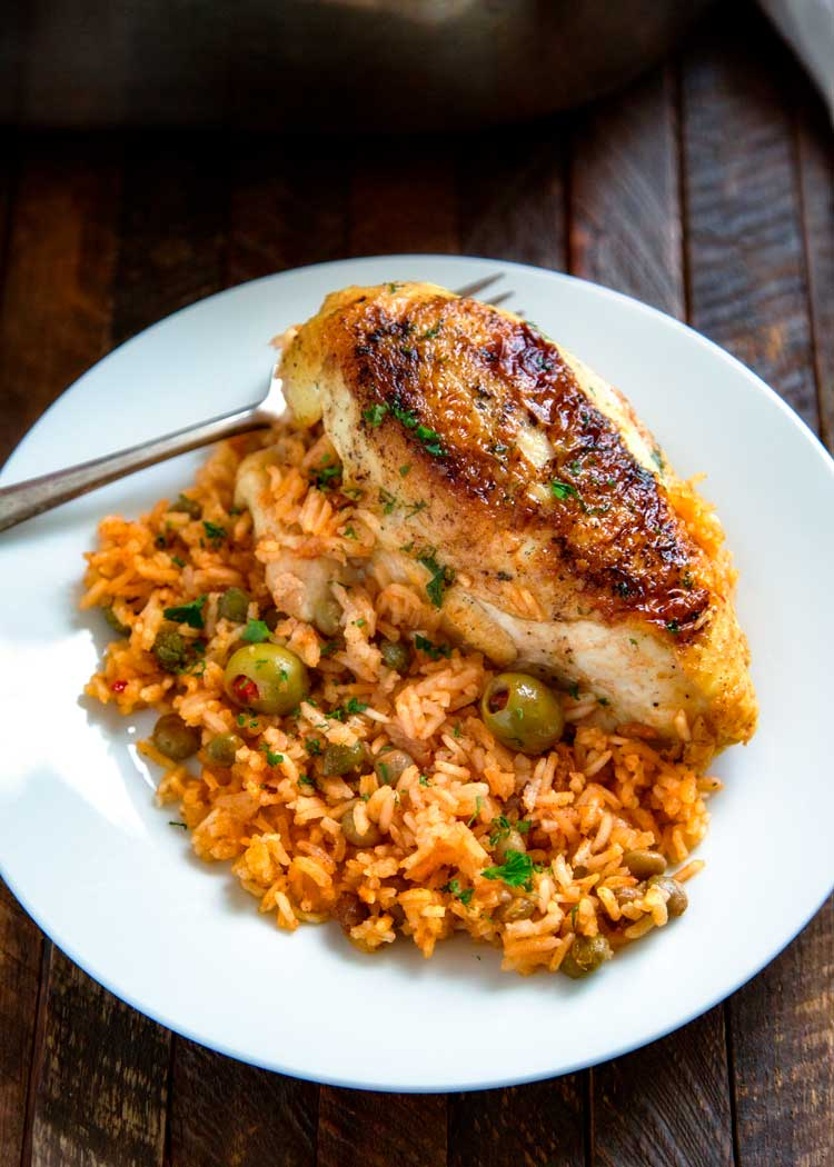 Puerto Rican Chicken and Rice is a Latin classic and packed with flavor, not heat. Browned chicken simmers in rice, flavorful sofrito, olives and capers. keviniscooking.com