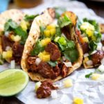 My Tacos Al Pastor version is done in the kitchen with marinated pork flavored with various chiles, pineapple, onion, garlic and cinnamon. With 2 cooking methods you can make this instead of carnitas tonight! keviniscooking.com