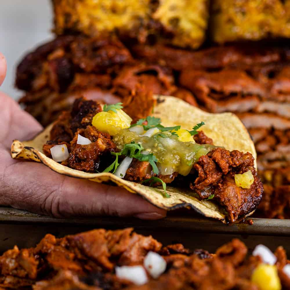 man's hand holding an authentic pork taco al pastor