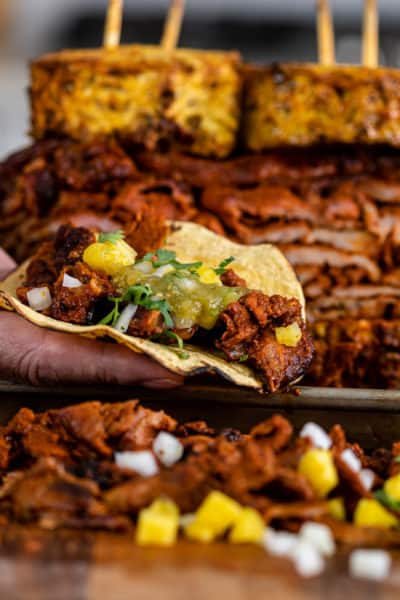al Pastor taco with grilled, stacked meat behind