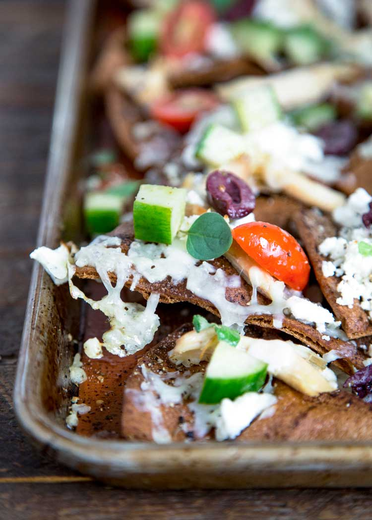 These Greek Styled Pita Chicken Nachos are a great party appetizer or main meal. Loaded with rotisserie chicken, a deconstructed Greek salad and lots of cheese! keviniscooking.com