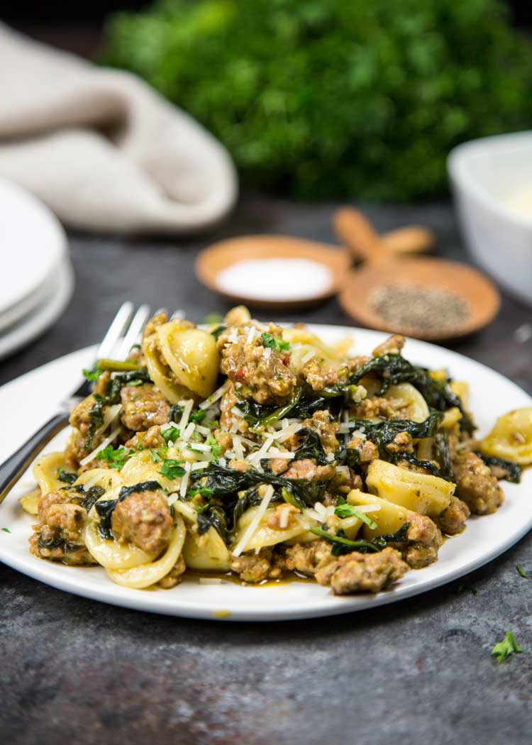 Orecchiette with Sausage and Spinach is a simple and rustic dish. Browned sausage, wine, pesto mixed with spinach and pasta all in under 30 minutes. Yum! keviniscooking.com