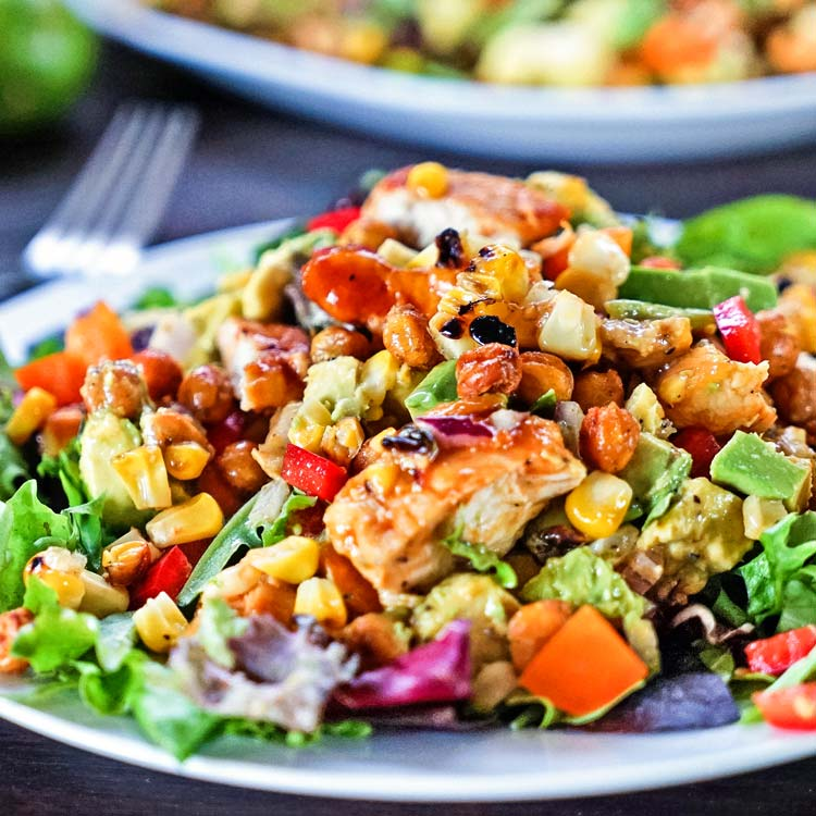This Southwest BBQ Chicken Salad has it all from grilled corn & BBQ chicken, avocado, bell peppers and dried apricots. A lime and honey dressing makes it! keviniscooking.com