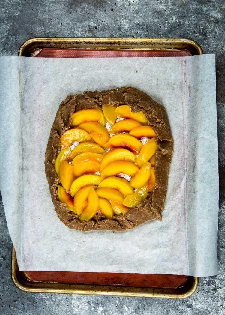 Ripe, juicy peaches are used in this whole wheat and ground hazelnut dough for a Summer free form pie. This Spiced Peach Galette is perfect for any BBQ or picnic party! keviniscooking.com