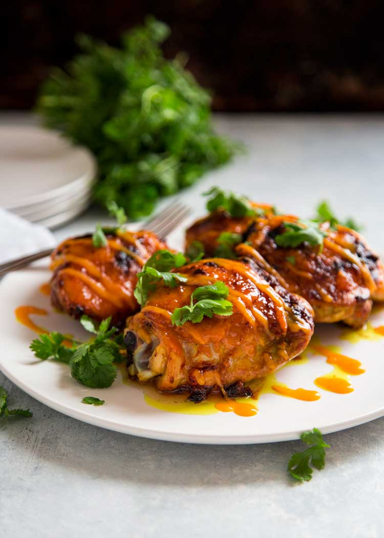 Rubbed with garlic, ginger and turmeric, these Mango Sriracha Roasted Chicken Thighs are glazed as they roast with a blended mango and sriracha chili sauce. keviniscooking.com