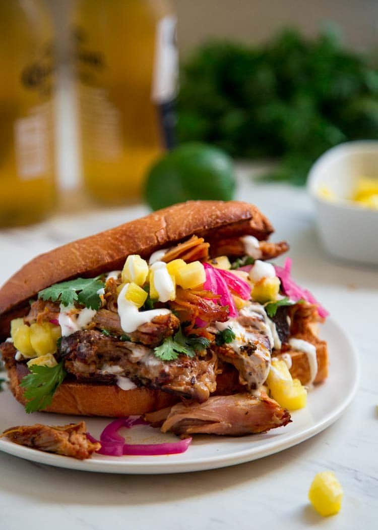 This Smoked Pulled Pork Sandwich is dry rubbed, smoked until tender then shredded and mixed with pineapple juice, Mexican oregano and guajillo peppers. So flavorful! keviniscooking.com