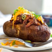 These Slow Cooker BBQ Beef Stuffed Potatoes are a perfect one pot meal made in the slow cooker. A wet rubbed chuck roast with BBQ sauce and the potatoes! keviniscooking.com