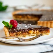 This Chocolate Macadamia Nut Tart has a pastry shell filled with macadamia nuts, caramel studded with chunks of ginger all topped with a chocolate ganache. keviniscooking.com
