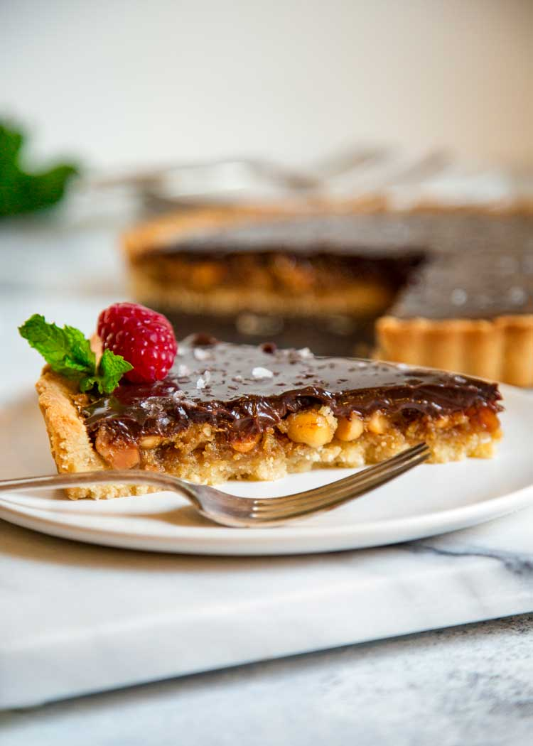 This Chocolate Macadamia Nut Tart has a buttery pastry shell filled with macadamia nuts, a caramel filling studded with chunks of ginger all topped with a chocolate ganache. keviniscooking.com