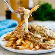 The Ultimate Chicken Poutine, better known as french fries smothered with gravy, is loaded with slow cooked, seasoned and shredded chicken and cheese curds. keviniscooking.com