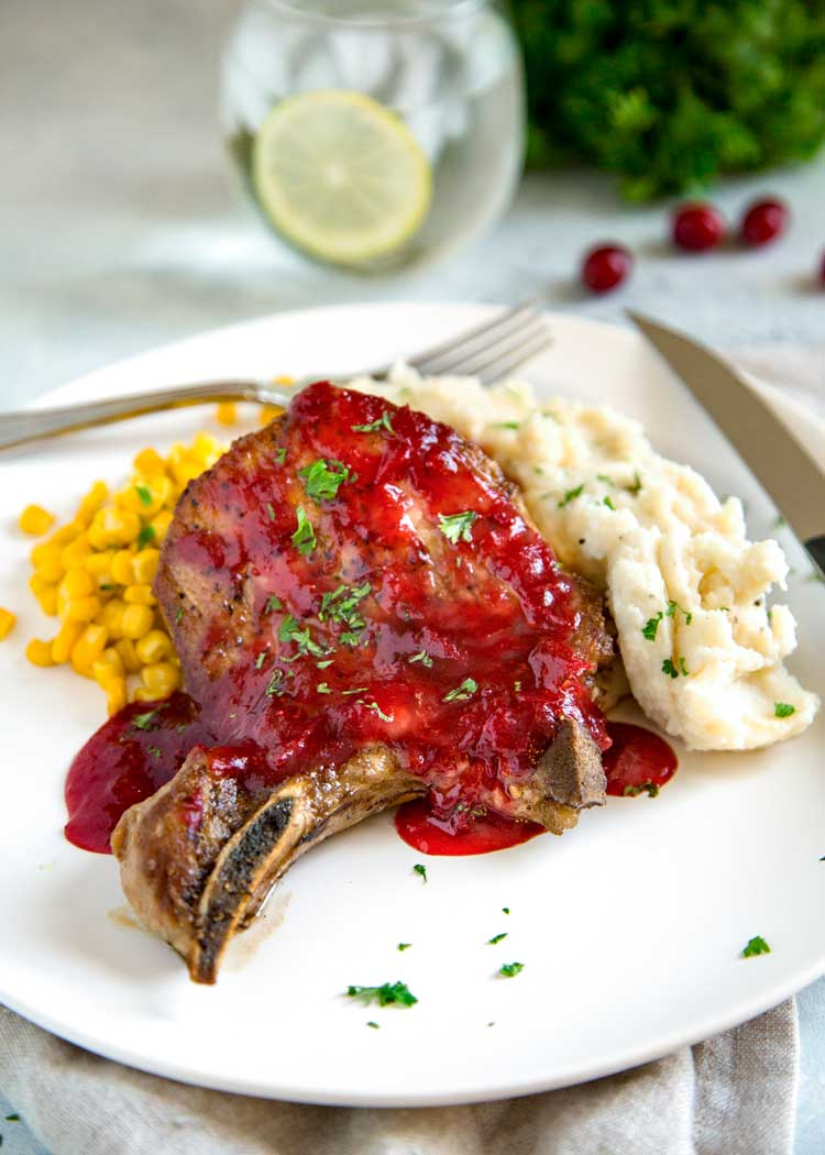 Cranberry Glazed Pork Loin Chops get seared and roasted to juicy perfection. The cranberry glaze includes honey, fresh ginger, orange juice and a chile. keviniscooking.com