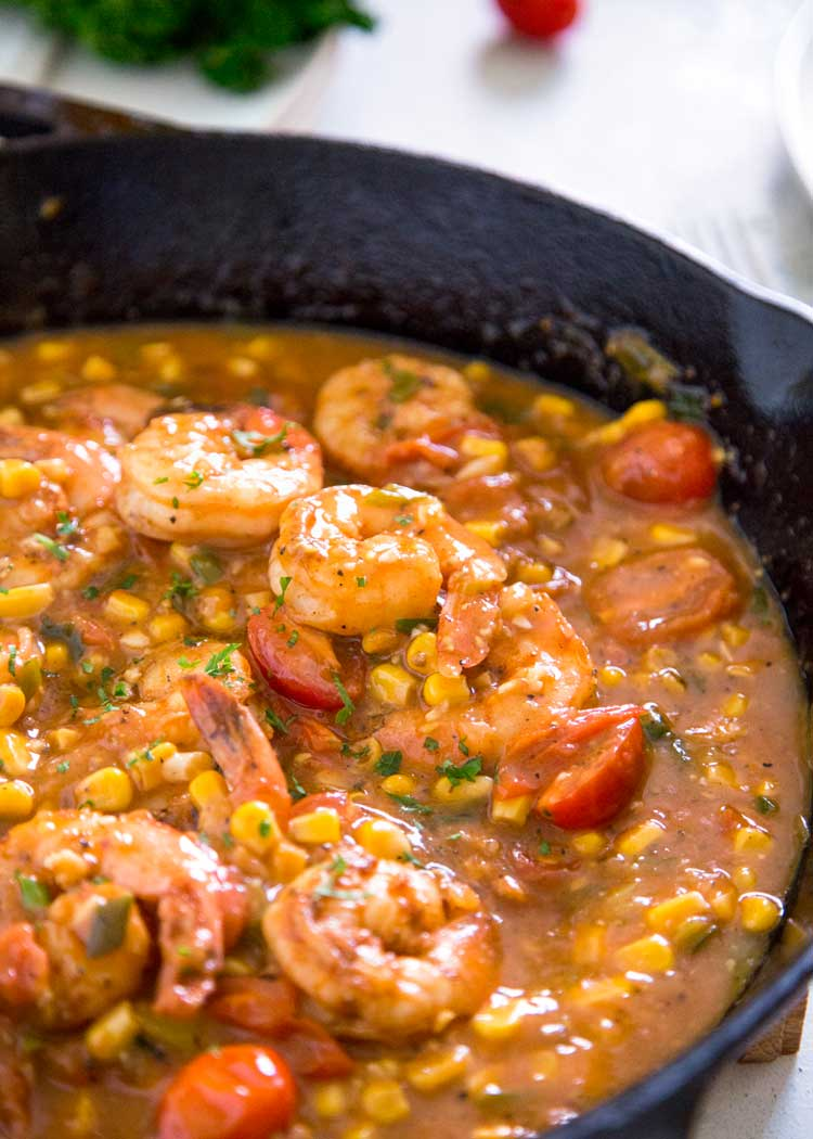 Cajun shrimp dinner with corn and tomatoes in a cast iron skillet